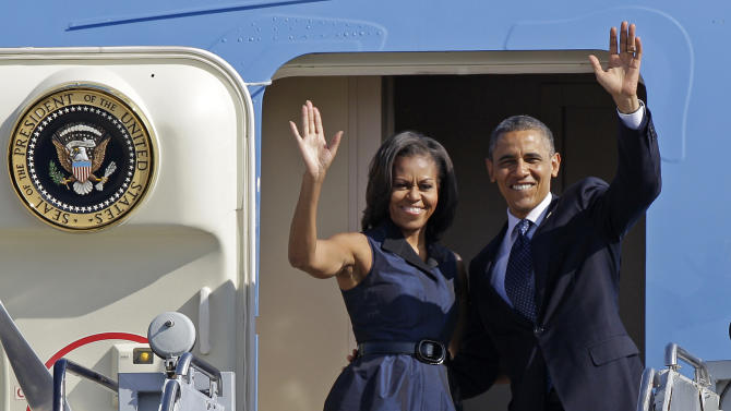 President Barack Obama and first lady Michelle Obama wave as they board Air Force One before leaving Charlotte, N.C., after the Democratic National Convention, Friday, Sept. 7, 2012. (AP Photo/Chuck Burton)