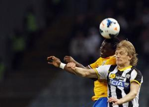 Juventus' Kwadwo Asamoah jumps for the ball with Udinese's Dusan Basta during their Italian Serie A soccer match at the Friuli stadium in Udine
