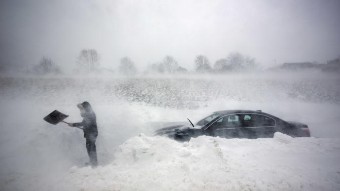 A woman digs out her car after it was blocked in by drifting snow during a blizzard, Saturday, Feb. 9, 2013, in Portland, Maine. The storm dumped more than 30 inches of snow as of Saturday afternoon, breaking the record for the biggest storm on record. (AP Photo/Robert F. Bukaty)
