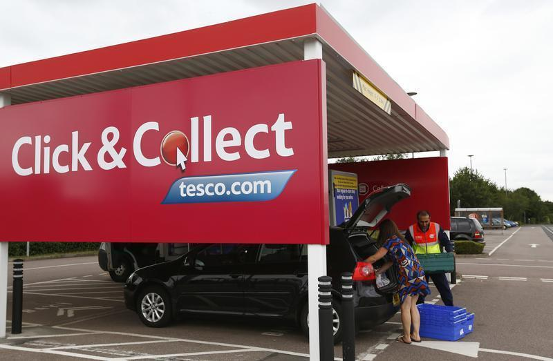 A worker helps a customer load her car with groceries at a Tesco click and collect point in Leicester