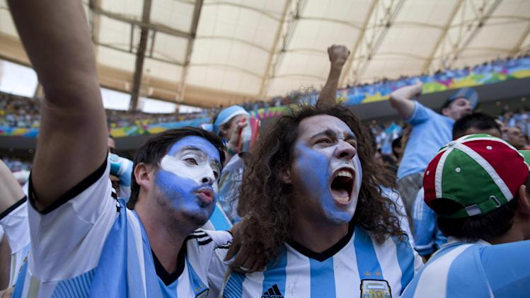 Soccer fans wearing the colors associated with Argentina's national soccer team, celebrate the opening goal scored against Belgium in a World Cup quarterfinals' match at the Estadio Nacional, in Brasilia, Brazil, Saturday, July 5, 2014. Gonzalo Higuain scored his first goal of this World Cup to give Argentina a 1-0 halftime lead over Belgium in their quarterfinal on Saturday
