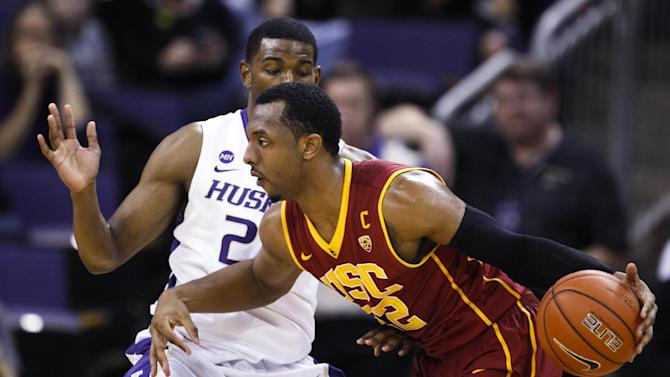 Southern California guard Byron Wesley (22) dribbles past Washington guard C.J. Wilcox (23) during the first half of an NCAA college basketball game, Saturday, March 8, 2014, in Seattle,