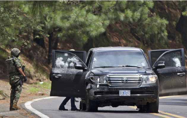 In this Aug. 24, 2012. file photo, an armored U.S. embassy vehicle is checked by military personal after it was attacked by unknown assailants on the highway leading to the city of Cuernavaca, near Tr