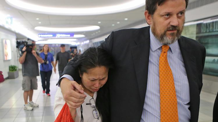 "Komdown ""Dow"" Boyer leaves with her lawyer, Jim Wyrsch, on Monday evening, June 23, 2014, at Lambert International Airport, after returning from Chicago where she was almost deported to Thailand in St. Louis. Dow Boyer was almost deported to Thailand earlier Monday after her conviction for stealing from her employer in Farmington. (AP Photo/St. Louis Post-Dispatch, J.B. Forbes) EDWARDSVILLE INTELLIGENCER OUT; THE ALTON TELEGRAPH OUT"