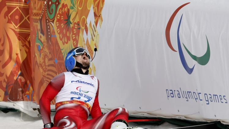 Switzerland's Hugo reacts after crashing at finish area during the men's alpine downhill for the visually impaired at the 2014 Sochi Paralympic Winter Games
