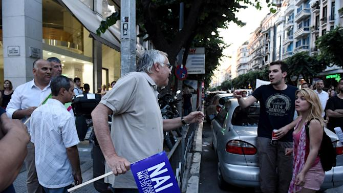 A demonstrator, left, supporting the yes vote argues with a couple supporting the no vote in the northern Greek port city of Thessaloniki, Thursday, July 2, 2015. The battle for Greek votes entered full swing Thursday ahead of a crucial weekend referendum that could decide whether the country falls out of the euro. (AP Photo/Giannis Papanikos)