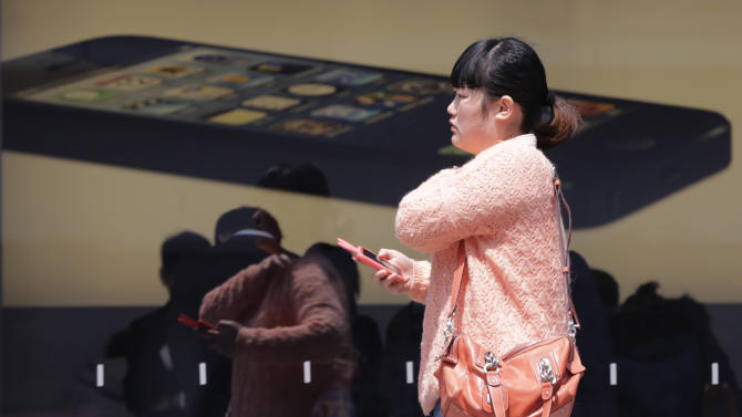 A woman walks by an advertisement of iPhone 5 at Apple store in Shanghai, China, Tuesday April 2, 2013. Apple apologized to Chinese consumers after government media attacked its repair policies for two weeks in a campaign that reeked of economic nationalism. (AP Photo/Eugene Hoshiko)