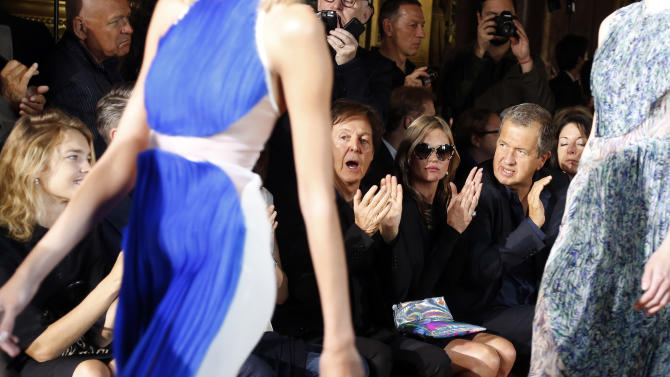 Sir Paul McCartney,  model Kate Moss and photographer Mario Testino, right, applaud as models wear creations for British fashion designer Stella McCartney's ready to wear Spring-Summer 2013 collection, presented in Paris, Monday, Oct.1, 2012. (AP Photo)