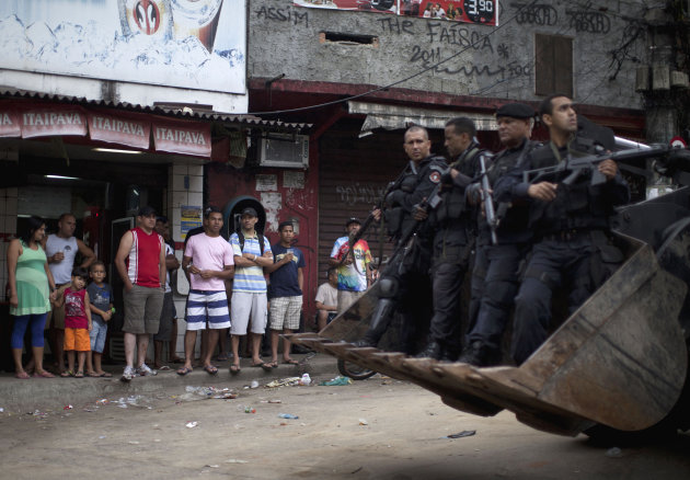 Residents watch police officers ride past in the shovel of a bulldozer in the Rocinha slum in Rio de Janeiro, Brazil, Sunday Nov. 13, 2011. Elite police units backed by armored military vehicles and h