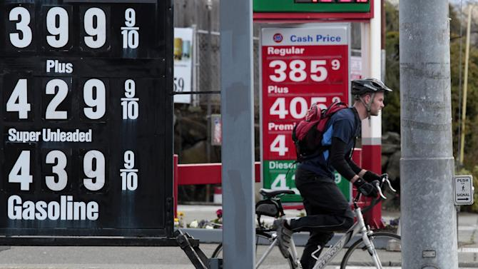 FILE - In this April 18, 2011 file photo, a bicyclist waits at an intersection between competing gas stations and multiple posted gas prices, in Seattle. The economy grew slightly faster in the spring than previously estimated but remained dangerously weak as the country struggled with surging gas prices and high unemployment.  (AP Photo/Elaine Thompson, File)