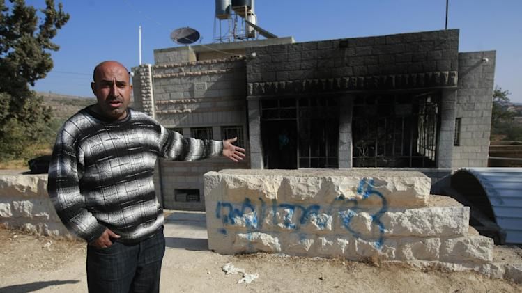 """A Palestinians man shows a damaged house with spray-painted the graffiti in Hebrew reading, """"Greetings from Eden. Revenge."""" in the village of Sinjil near the West Bank City of Ramallah, Thursday, Nov. 14, 2013. Israeli police said vandals have set fire to a Palestinian home in the West Bank and scrawled graffiti on it. Police spokesman said the incident appeared to have come in response to the killing of an Israeli soldier, Eden Attias, on Wednesday by a Palestinian teenager. (AP Photo/Majdi Mohammed)"""