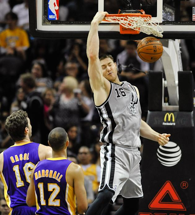 San Antonio Spurs center Aron Baynes dunks in front of Los Angeles Lakers' Pau Gasol and Kendall Marshall in the first half of an NBA basketball game Friday, March 14, 2014 in San Antonio. The Spu