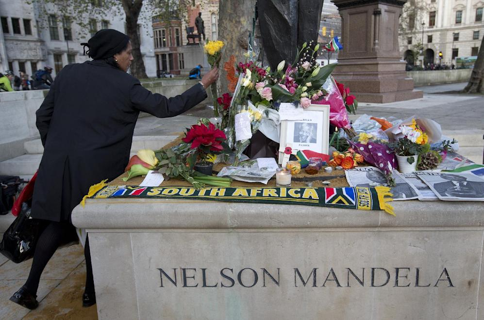 A woman lays flowers in tribute at the foot of the Nelson Mandela statue in Parliament Square, in London, Friday, Dec. 6, 2013. Mandela passed away Thursday night after a long illness. He was 95. As word of Mandela's death spread, current and former presidents, athletes and entertainers, and people around the world spoke about the life and legacy of the former South African leader. (AP Photo/Alastair Grant)