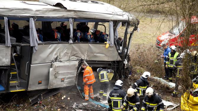 Police officers go over evidence and personal items at the site of a bus crash in Ranst, Belgium on Sunday, April 14, 2013. The Polish bus carrying Russian youngsters crashed through guardrails and off a highway onto a field below near the port city of Antwerp on Sunday, killing at least five people and leaving five more critically injured. (AP Photo/Virginia Mayo)
