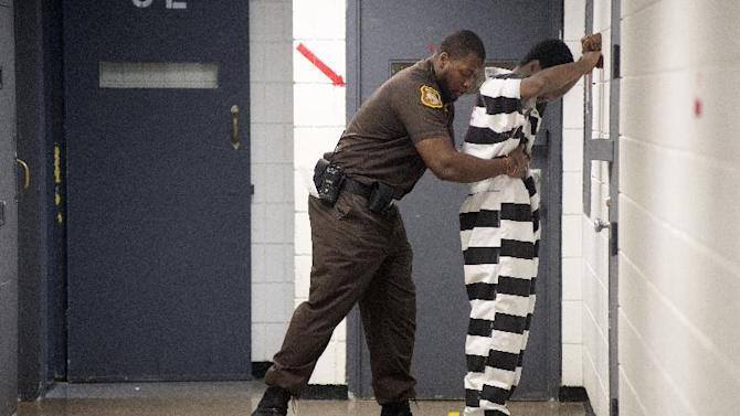Corrections Officer Terence Moore frisks an inmate before the inmate meets with his attorney at the Saginaw County Jail, Friday, July 18, 2014 in Saginaw, Mich. The Saginaw County Sheriff's Department has purchased new jumpsuits, with black and white stripes, for some of the inmates at the jail. (AP Photo/The Saginaw News/MLive.com, Jeff Schrier)