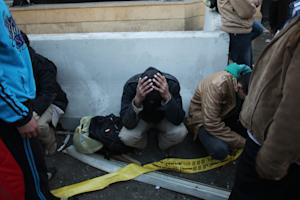 Egyptian police officers sit on the street after a …