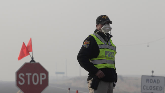 """A police officer wears a mask while manning a checkpoint as smoke from the Wallow Fire fills the air near Springerville, Ariz., Saturday, June 11, 2011. Smoke from the huge wildfire in eastern Arizona that has claimed more than 30 homes and forced nearly 10,000 people to flee has officials worried about serious health impacts to residents and firefighters as tiny particles of soot in the air reached """"astronomical"""" levels. (AP Photo/Jae C. Hong)"""