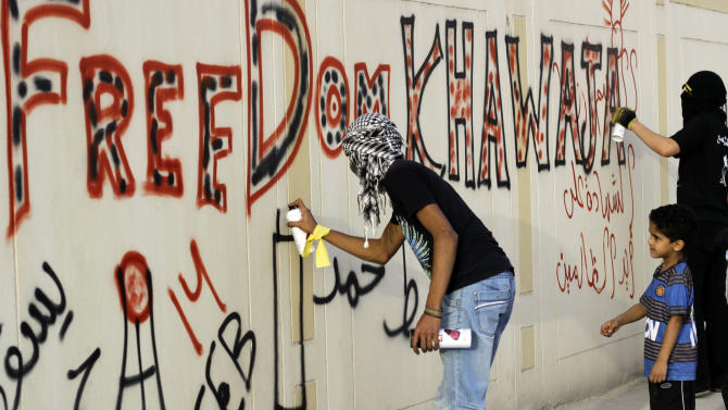 """Anti-government protesters spray graffiti on a wall in Sanabis, Bahrain, on Tuesday, April 24, 2012, calling for the release of jailed human rights activist Abdulhadi al-Khawaja, who has been on a hunger strike for more than 70 days. Witnesses said police in Bahrain have used tear gas and water cannons to disperse hundreds of protesters calling for al-Khawaja's release. Arabic on the walls reads: """"Down Hamad,"""" referring to Bahrain's king, and """"Martyrdom at  the hands of the unjust."""" (AP Photo/Hasan Jamali)"""