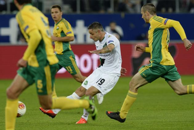 FC St. Gallen's Mario Mutsch, center, and Kuban Krasnodar's Artur Tlisov, right, challenge  for the ball during their UEFA Europa League Group A  soccer match between Switzerland's FC St. Gallen and R
