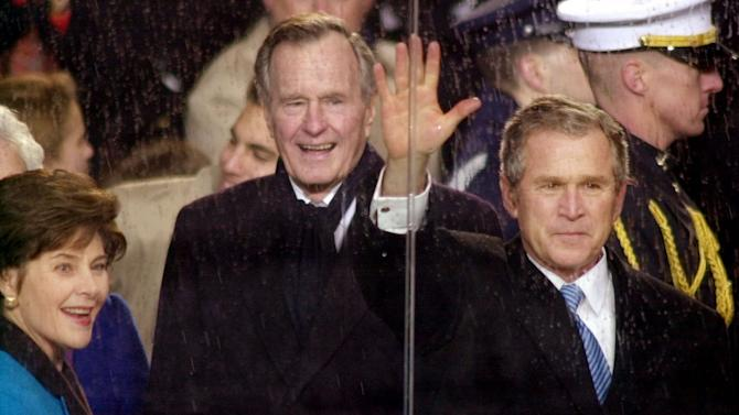 FILE - In this Jan. 20, 2001, file photo, standing in the rain, President George W. Bush waves as he watches his inaugural parade pass by the White House viewing stand in Washington, Saturday afternoon, Jan. 20, 2001.  With him are his wife and first lady Laura Bush and his father,  former President George H.W. Bush. The inauguration of the U.S. president is traditionally a highly-scripted celebration, with seating charts, schedules, dress rehearsals, and planning committees that map each moment of the history-making day from start to finish. But sometimes the unexpected happens. The last time the nation had seen a president's father live long enough to attend his son's inauguration was 40 years earlier, when Joseph Kennedy watched the inauguration of President John F. Kennedy in 1961. (AP Photo/Stephan Savoia)