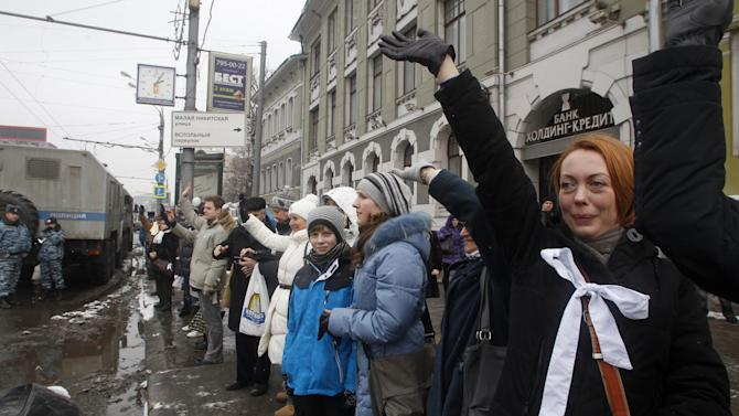 People stand along Garden Ring avenue wearing white ribbon as a symbol of peaceful protest and wave hands to drivers during opposition protest in Moscow, Russia, Sunday, Feb. 26, 2012.  Thousands of people are holding hands to form a 16-kilometer (10-mile) human chain encircling central Moscow in the latest protest against Russian Prime Minister Vladimir Putin. Opposition activists estimated that they needed 34,000 people to complete the chain along the Garden Ring on Sunday and they appeared to have succeeded or come close. (AP Photo/Mikhail Metzel)