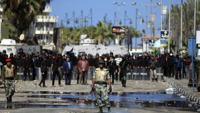 An Egyptian army officer stands guard between riot police and protesters, not seen, during clashes near the state security building in Port Said, Egypt, Wednesday, March 6, 2013. Clashes between protesters and police have broken out in this restive Egyptian port city despite efforts by the military to separate the two sides. (AP Photo/Khalil Hamra)