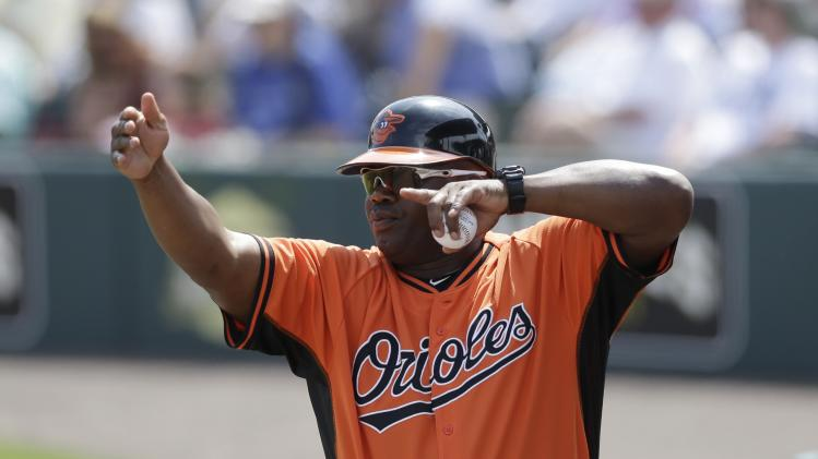 Baltimore Orioles first base coach Wayne Kirby signals from the dugout during a spring exhibition baseball game against the Pittsburgh Pirates in Bradenton, Fla., Monday, March 10, 2014. (AP Photo/Carlos Osorio)