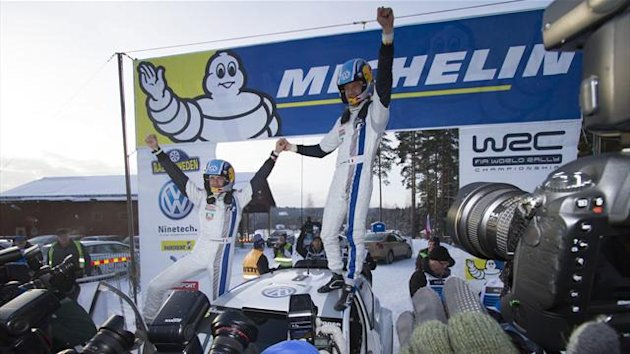 France's Sebastien Ogier (R) and his co-driver France's Julien Ingrassa celebrate as they stand on their VW Polo WRC after winning the Sweden Rally of the second round of the FIA World Rally Championship in Hagfors (Reuters)