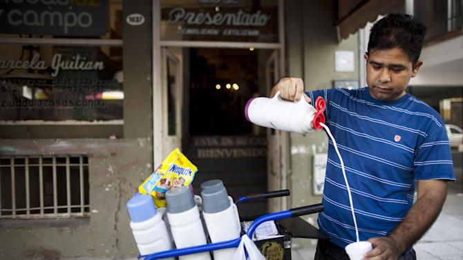 "Freddy Lopez, who works selling coffee from his cart in the street, serves a 5 peso cup of coffee with milk in Buenos Aires, Argentina, Thursday, Jan. 17, 2013. According to the government, it only takes six pesos a day to eat in Argentina. But on the streets of the capital, 6 pesos doesn't stretch beyond a pack of chewing gum, or a cup of yogurt, or a single ""alfajor"": the country's traditional caramel-and-chocolate cookies. (AP Photo/Natacha Pisarenko)"