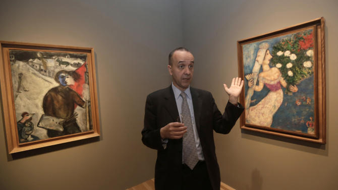 """In this photo taken Feb. 13, 2013, museum curator Olivier Meslay talks about paintings by artist Marc Chagall included in the """"Chagall: Beyond Color,"""" exhibit during a preview at the Dallas Museum of Art Wednesday, Feb. 13, 2013, in Dallas. This will be the only U.S. venue to host the exhibit that opens to the public on Sunday. (AP Photo/LM Otero)"""