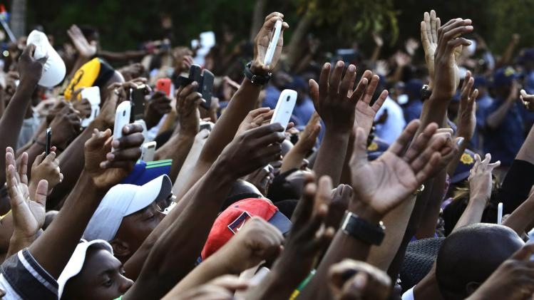 The crowd waves as the hearse carrying former South African President Nelson Mandela departs the Union Buildings in Pretoria for the final time