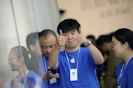 <p>Staff greet customers at Apple's new store in Beijing on October 20. Enthusiasm for the company's gadgets among the country's fast-growing consumer class was clear Saturday as shoppers quickly packed out the new shop shortly after it opened at 9:00 am.</p>