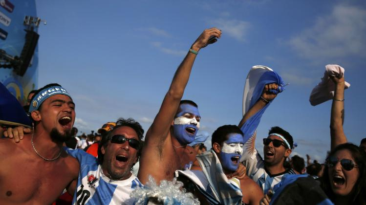 Argentinian soccer fans celebrate a goal as they watch the 2014 World Cup soccer match between Argentina and Iran on a large screen at Copacabana beach in Rio de Janeiro