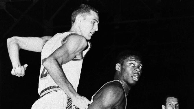 FILE - In this Feb. 5, 1961, file photo, Cincinnati Royals' Oscar Robertson, center, looks back as Los Angeles Lakers' Jerry West defends during their NBA basketball game in Morgantown, W.Va. (AP Photo, File)