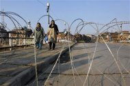 Kashmir Muslim woman carry groceries as they cross a bridge behind coils of concertina wire during restrictions in Srinagar February 9, 2013. India has executed a Kashmiri militant who was sentenced to death 10 years ago for an attack on the Indian parliament in 2001, a senior interior ministry official said on Saturday. The country's president rejected a mercy petition from Mohammad Afzal Guru and he was hung at dawn, TV channels said. Strict restrictions on people's movements was imposed in major towns of Indian Kashmir early on Saturday in anticipation of protests against the hanging. REUTERS/Danish Ismail