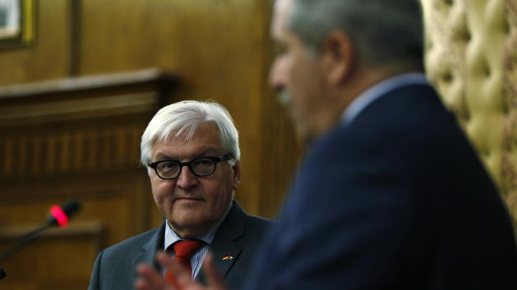 German Foreign Minister Steinmeier listens to his Jordanian counterpart Judeh during their joint news conference at the Ministry of Foreign Affairs in Amman