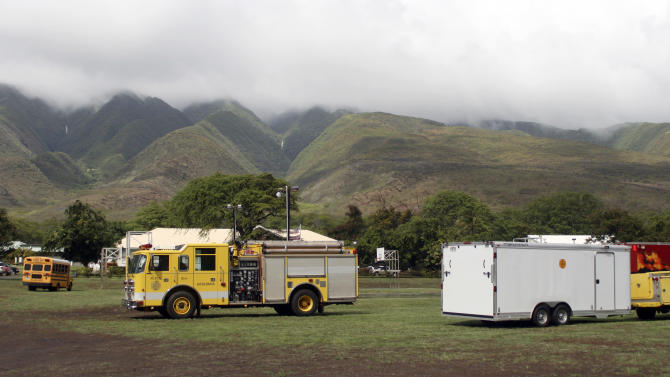 Emergency vehicles from are positioned near Kilohana Elementary School on Molokai, in Hawaii, Thursday, Nov. 10, 2011, after a helicopter taking four tourists on an excursion over the island crashed into a mountainside near the school killing all of the tourists and the pilot, according to authorities. (AP Photo/Joey Salamon)