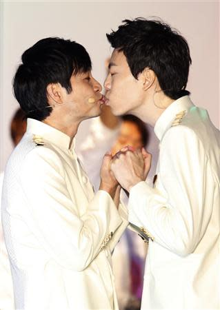 South Korean film director Kim Jho Gwang-soo kisses his partner Kim Seung-hwan during their wedding ceremony in central Seoul