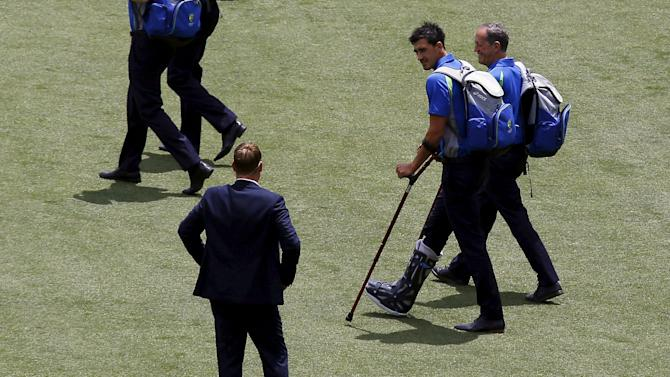 Injured Australian bowler Starc talks with Warne as he arrives with the team before the start of the second day of the third cricket test match against New Zealand at the Adelaide Oval, in South Australia