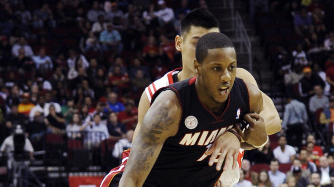 Miami Heat's Mario Chalmers, front, is wrapped up by Houston Rockets' Jeremy Lin in the first half of an NBA basketball game, Monday, Nov. 12, 2012, in Houston. (AP Photo/Pat Sullivan)