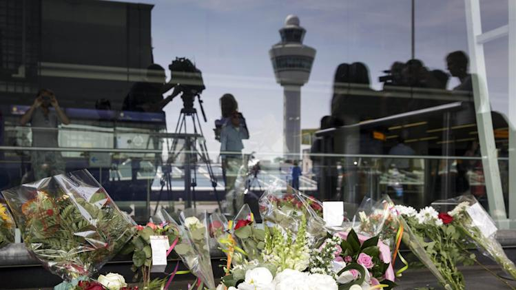 Schiphol traffic tower is reflected in a window behind flowers placed outside Schiphol airport in Amsterdam, Friday, July 18, 2014. The attack on a Malaysian jetliner Thursday afternoon killed 298 people from nearly a dozen nations, more than half being Dutch, including vacationers, students and a large contingent of scientists heading to an AIDS conference in Australia. (AP Photo/Phil Nijhuis)