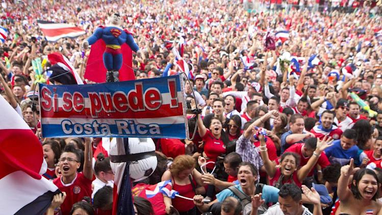 "Costa Rica soccer fans celebrate a goal against Greece as they watch their team's World Cup round of 16 match on TV set up in a public square in San Jose, Costa Rica, Sunday, June 29, 2014. The sign reads in Spanish ""Yes we can Costa Rica!"""