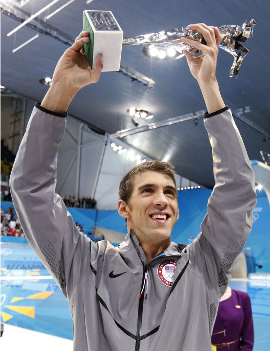 Michael Phelps of the U.S. holds up his trophy awarded to him by FINA honouring him as the most decorated Olympian of all time during the London 2012 Olympic Games at the Aquatics Centre