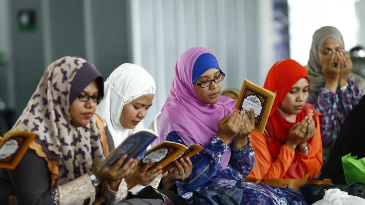 Women read booklets containing verses from the Koran during a special prayer for victims of Malaysia Airlines Flight MH17, inside the Tuanku Mizan Zainal Abidin mosque in Putrajaya