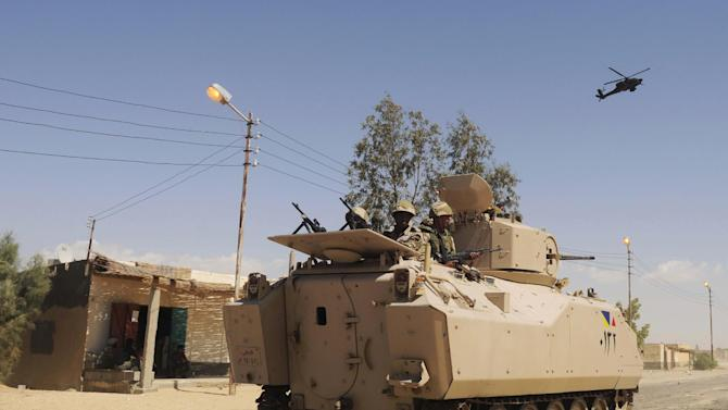 FILE - In this Tuesday, May 21, 2013, file photo, Egyptian Army soldiers patrol in an armored vehicle backed by a helicopter gunship during a sweep through villages in Sheikh Zuweyid, northern Sinai, Egypt. A military official said Saturday, Sept. 7, 2013, Egyptian helicopters and tanks are attacking Islamic militants in villages in the northern Sinai Peninsula. The Saturday assault came after Egypt deployed a column of armored vehicles and trucks carrying infantry into the region, a militant stronghold, in a major new counterinsurgency offensive, the official said. (AP Photo, File)