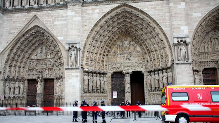 Police officers stand guard in front of Notre Dame Cathedral, in Paris, Tuesday, May 21, 2013. Notre Dame has been evacuated after a man committed suicide in the 850-year-old monument and tourist attraction. (AP Photo/Thibault Camus)