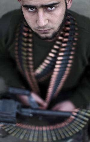 In this Monday, Dec. 17, 2012 photo, Syrian rebel fighter Ibrahim Iaaa, 20, a former construction worker, poses for a picture following a training session in Maaret Ikhwan, near Idlib, Syria. The new Syrian rebel chief, a defected army general who spent months in exile, says he has begun operating inside Syria to unite autonomous anti-regime militias for what he hopes will be the final push against President Bashar Assad. (AP Photo/Muhammed Muheisen)