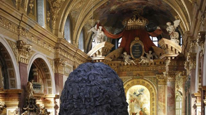 "Tourists stand around the artwork ""To be in Limbo"" in the Jesuit church in Vienna"