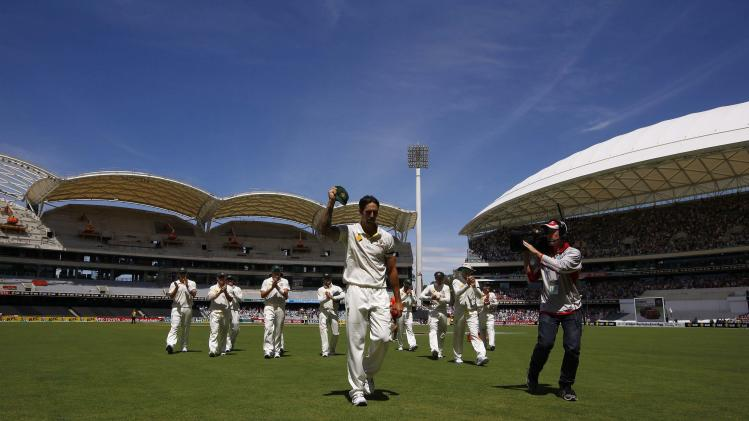 Australia's Johnson acknowledges the crowd with his cap after taking seven wickets in the inning as the team walks off the field during the third day of the second Ashes test cricket match in Adelaide