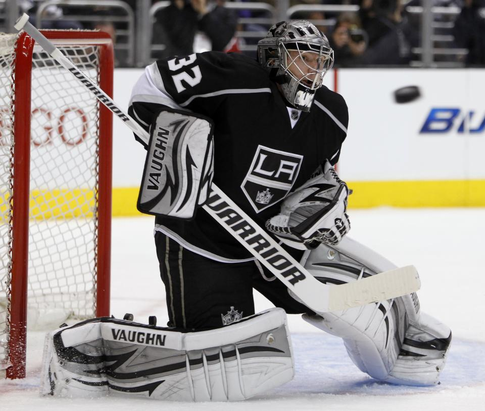 Los Angeles Kings goalie Jonathan Quick (32) keeps his eyes on the puck to make a stop against the Vancouver Canucks during the first period of Game 3 in a first-round NHL Stanley Cup playoff series in Los Angeles, Sunday, April 15, 2012.  (AP Photo/Alex Gallardo)